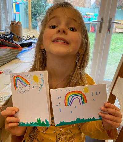 Picture of child Eloise with postcards that she has made