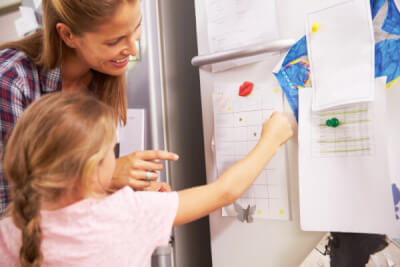 Photograph of parent or carer and child putting a list onto a fridge