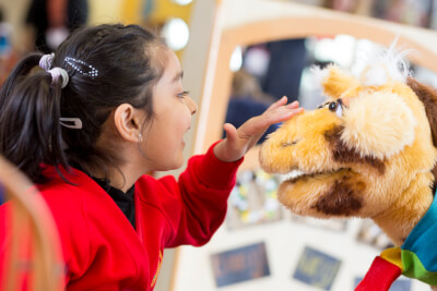 photograph of child stroking giraffe puppet and both smiling